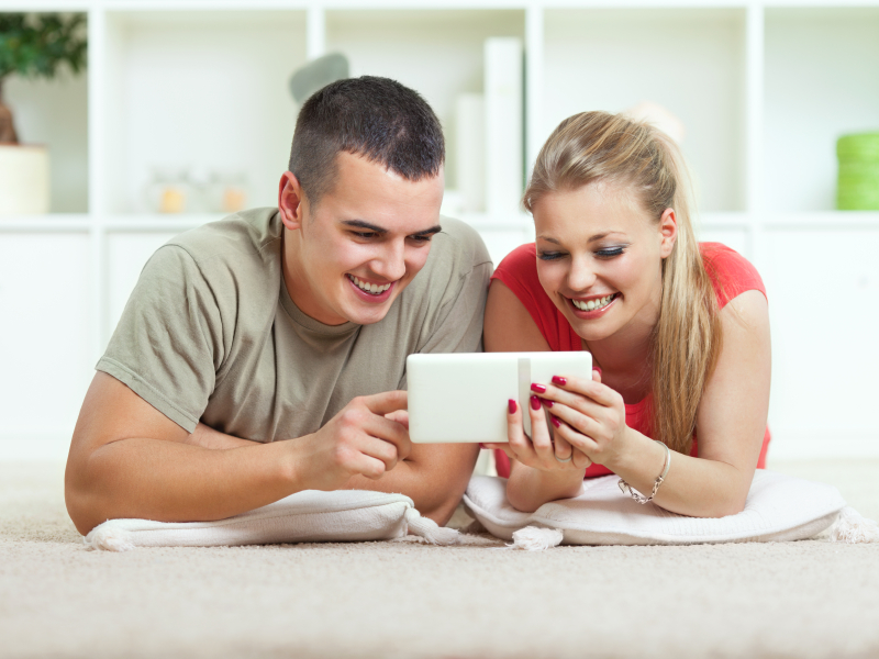Young couple using digital tablet at home.